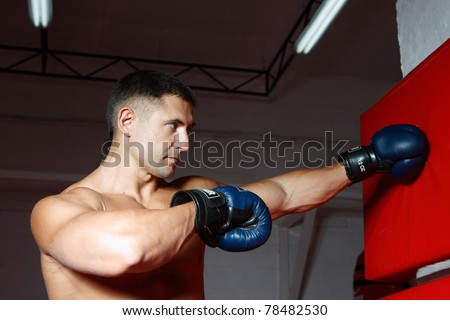 The young guy in the sports form boxes in gloves a pear