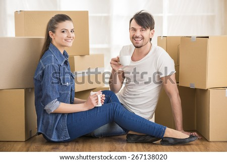 The young happy couple drinking tea and coffe. Moving, purchase of new habitation. - stock photo