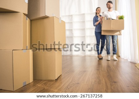 The young happy couple looking around their new apartment. Moving, purchase of new habitation. - stock photo