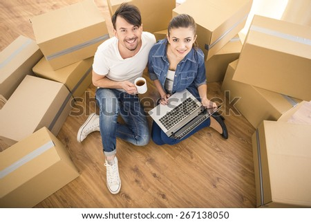 The young happy couple searching for apartments with laptop. Moving, purchase of new habitation. - stock photo