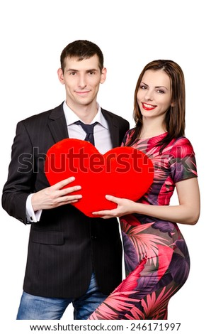 The young happy couple with red heart in their arms on the white background
