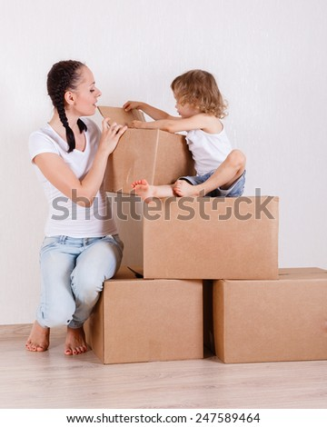 The young happy mother and daughter sit in a room on a lot of the boxes. Moving, purchase of new habitation or repair of a room. - stock photo