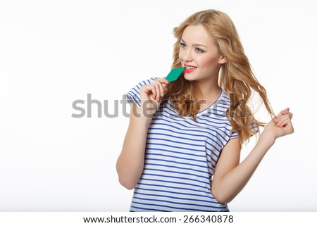 The young happy woman, biting the card of the blank credit, on a white background - stock photo