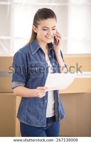 The young happy woman calling transport company to move in new house. - stock photo