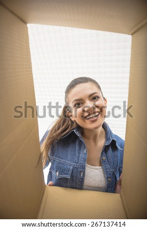 The young happy woman looking in box. Moving, purchase of new habitation. - stock photo