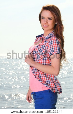 The young happy woman on a beach sea and sky vacation