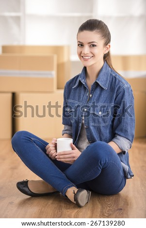 The young happy woman siting in a room near boxes. Moving, purchase of new habitation. - stock photo