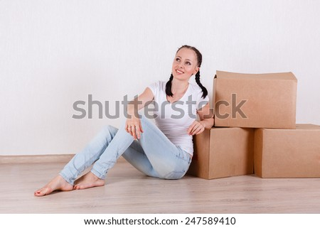 The young happy woman sits in a room near  boxes. Moving, purchase of new habitation. - stock photo