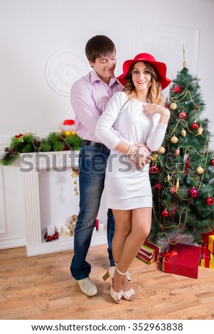 The young loving couple on Christmas, in the white room in the Christmas decor, full length. - stock photo