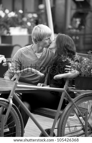 The young man and girl in the cafe. Photo in black and white style. - stock photo