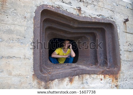 The young man and mobile in an embrasure of old military strengthening (1945 eyar). - stock photo
