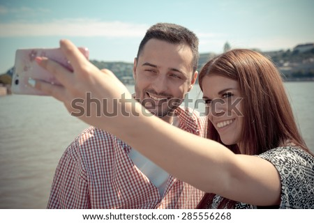 The young man and the attractive woman take a selfie next to the Danube