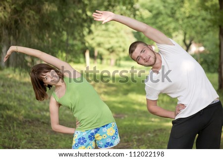 The young man and the girl are engaged in gymnastics - stock photo