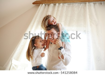 The young man cheerfully spends time with the little daughters. Younger girl sits at the father on shoulders, another trying to climb the dad. Children and father delighted with a play.
