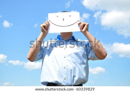 The young man covered his face with a sheet of paper with a picture - stock photo