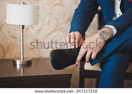 The young man dresses boots. - stock photo