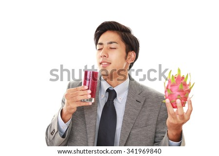 The young man drinking a glass of juice - stock photo