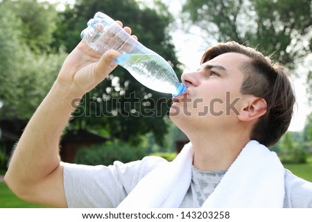 The young man drinks water from a bottle - stock photo