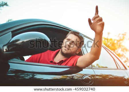 The young man driving the car angry, stuck in a traffic jam - stock photo