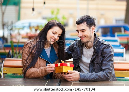 The young man gives a gift to a young girl in the cafe