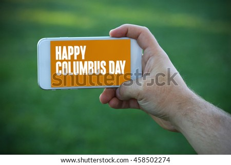 The young man holds the hand Happy Columbus Day by smartphone - stock photo