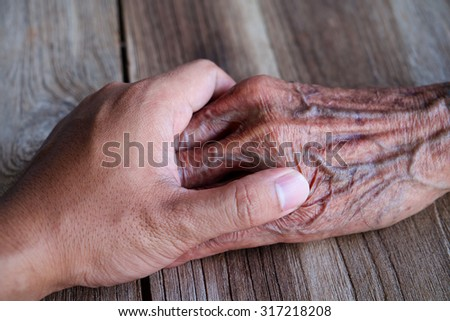 The young man holds the hand of the old man's hand. - stock photo