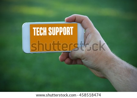 The young man holds the hand Tech Support by smartphone - stock photo