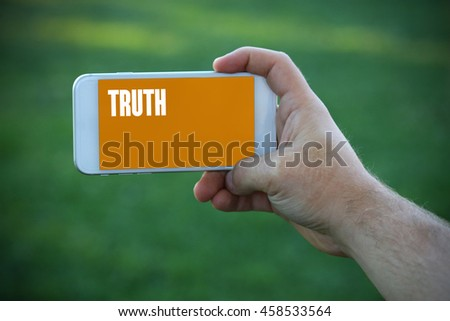 The young man holds the hand Truth by smartphone - stock photo