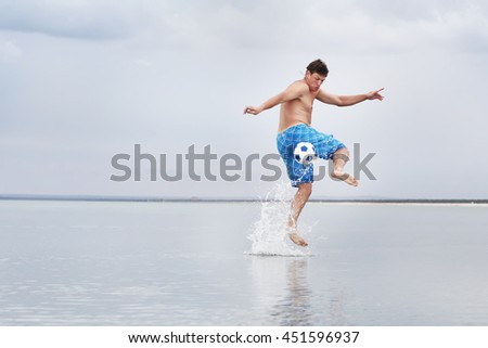 The young man in a jump with a ball in water at the sea