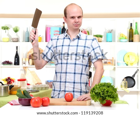 The young man in kitchen preparing - stock photo