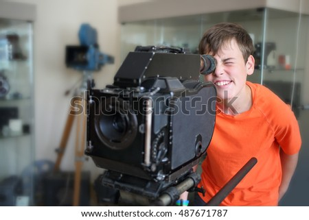 The young man in orange t-shirt looking at the old camera in a museum