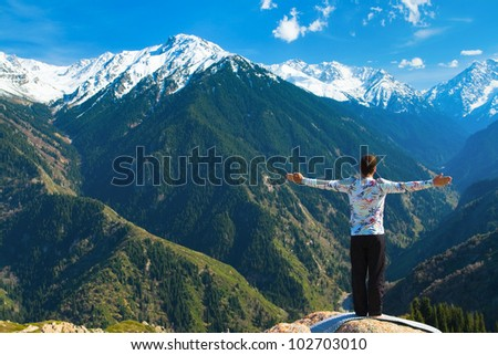 The young man is doing a yoga asana �¢??Sun Salution�¢?� on the summit. On the background is a range of high tops of mountains. - stock photo