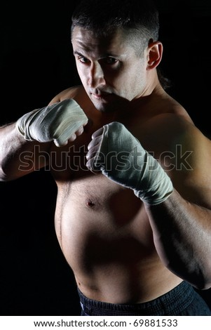 The young man is engaged in boxing in sports hall and beats on a pear - stock photo