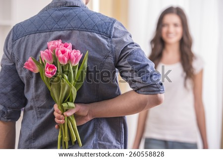 The young man is hiding flowers behind their backs to his girlfriend at home. - stock photo