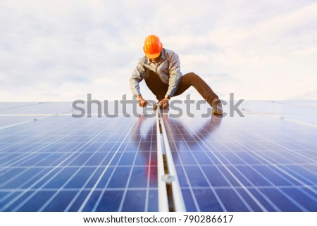 The young man is repairing the solar panel at the station.