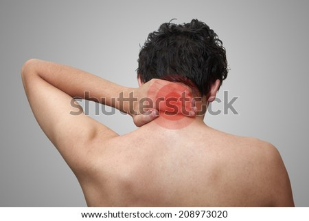 The young man keeps for neck. On a grey background - stock photo
