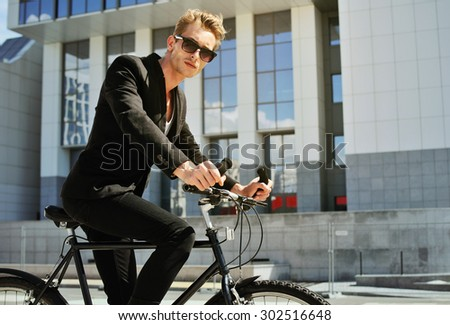 The young man on bicycle at the street - stock photo