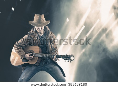 The young man playing guitar on the stage - stock photo