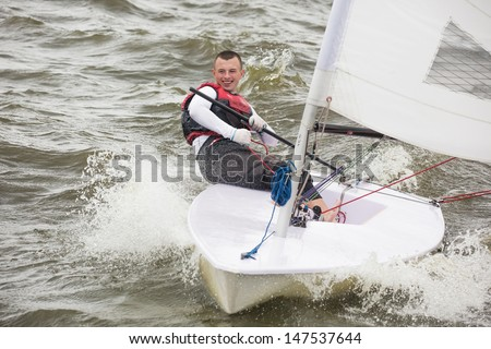 The young man quickly moves on a sports yacht - stock photo