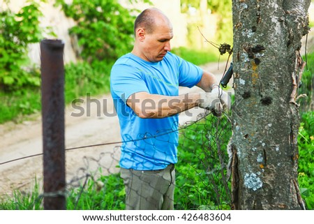 The young man repairs a fence outdoor.