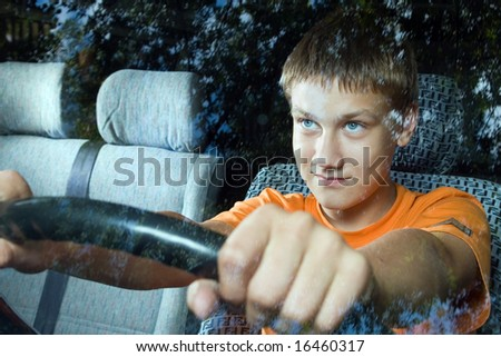 The young man sits at a rudder of a minibus - stock photo
