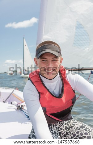 The young man sits in a sports yacht - stock photo
