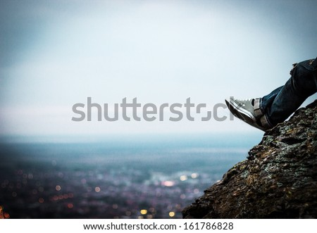 The young man sits on a rock above the city in the sunset - stock photo