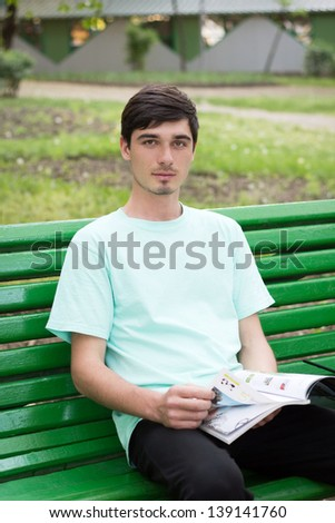 The young man sits on a shop and reads log in park - stock photo