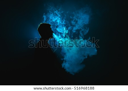 The young man smoke an electronic cigarette against the background of the blue light