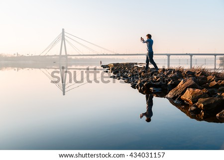 The young man  take photo of the view with river and bridge with smart phone at dawn, in a morning