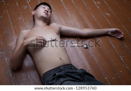 The young man the addict lies on a floor without consciousness from overdose - stock photo