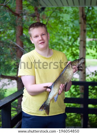 The young man, the fisherman, with the caught pike  - stock photo