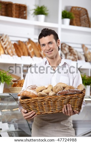 The young man with a basket of rolls in shop - stock photo
