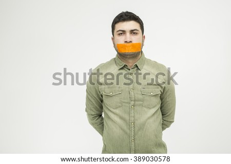 The young man with duct tape over his mouth. - stock photo